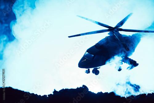 Fototapeta Battle scene with toy helicopter above battleground with smoke on blue background obraz