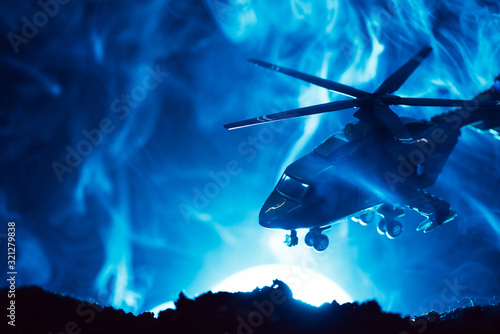 Fototapeta Battle scene with toy helicopter in smoke with moon on blue background obraz