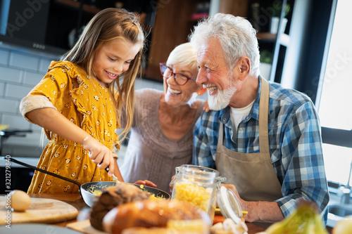Photo Happy grandchildrens girls having breakfast with her grandparents