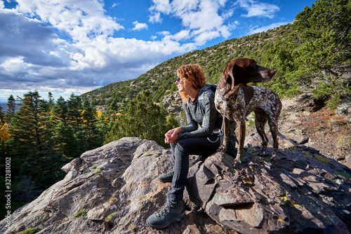 a young woman and her dog hiking to the top of a mountain Canvas Print