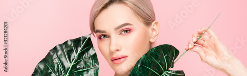 Fotomural panoramic shot of attractive girl with pink makeup isolated on pink with green l