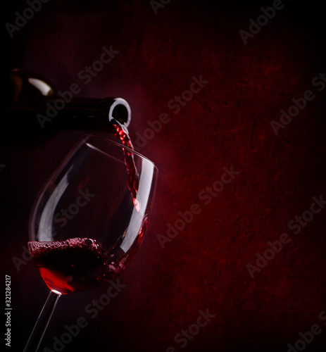 Obraz na plátně Red wine pouring in wineglass from bottle over dark background.