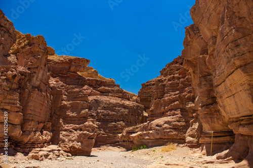 soft focus desert sand stone canyon rocks passage trail between walls foreshortening from below on vivid blue sky background