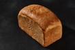 Leinwandbild Motiv Whole loaf of fresh, palatable baked white bread against black background with copy space. Close-up