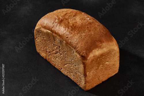 Fotografia Whole loaf of fresh, palatable baked white bread against black background with copy space
