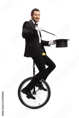 Magician with a wand riding a unicycle and smiling at camera Wallpaper Mural