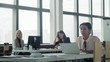 Female multi ethnic manager works in office with laptop and communicates with employees. In the background are colleagues. Coworking. Office life. Business space. Hand camera