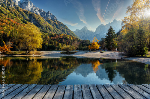 Wall mural - Amazing nature Landscape in Julian Alps during sunset. Lake Jasna near Kranjska Gora, Slovenia. Crystal clear alpine with colorful trees and mountain peaks in background. Triglav national park