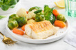 Fried cod fillet with vegetables: baby carrots, brussels sprouts, broccoli, cauliflower and corn salad on a white plate. Healthy food. Selective focus