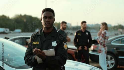 Obraz na plátne Confident serene african american cop with papers looking on camera looking serious leaning on the police car