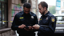 Police At Raid. Close-up Two Handsome Policemen Searching On Smartphones Tracking A Criminal Online. Friendly Colleagues Cops At Police Investigation Area In The City Street.