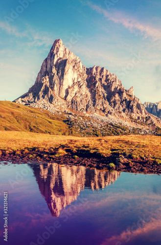 Wall mural - Scenic image of mountains during sunset. Great view of Giau Pass, Italian Dolomites, with the peaks of teh mountain and colorful sky reflected in a small lake, Italy.