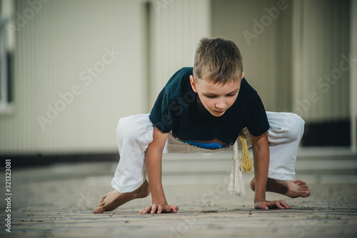 Fototapeta the boy is engaged in capoeira on the street