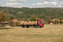 Truck Loaded With Round Hay Bales On Countryside Meadow