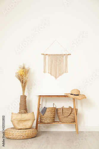 Fototapeta Stylish room with wooden table and wicker bags near white wall. Interior design obraz