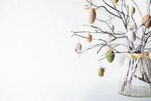 Still Life With Tree Branches Decorated With Easter Eggs And Feathers In Glass Vase