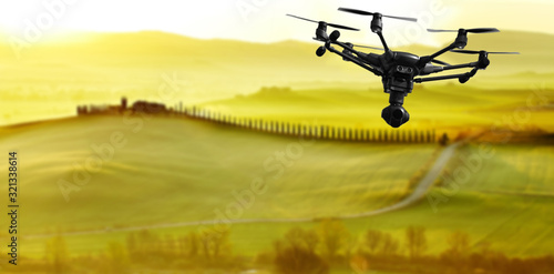 Obraz A flying drone with camera with blured hills of Tuscany in the background - fototapety do salonu