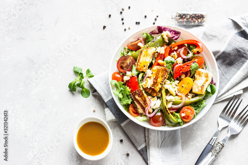 Fototapeta Vegetable salad cherry tomatoes, baked pepper, salad mix and onion with grilled haloumi (halloumi) cheese. Keto diet, healthy food. Light grey stone background. Top view. obraz