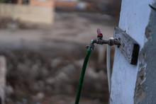 Water Faucet With A Hose Connected To A Metal Screed