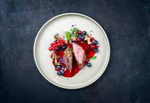 Fried Dry Aged Venison Tenderloin Fillet Medallion Steak Natural With Mushrooms And Forest Berries As Closeup On A Modern Design Plate With Copy Space