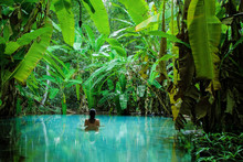 A Girl Stands In A Natural Pool Surrounded By Banana Tree's Leafs