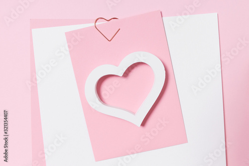 Empty template for romantic letters on a pink background. White feather with gold plating. Real photo, flat lay. Copy space for text.