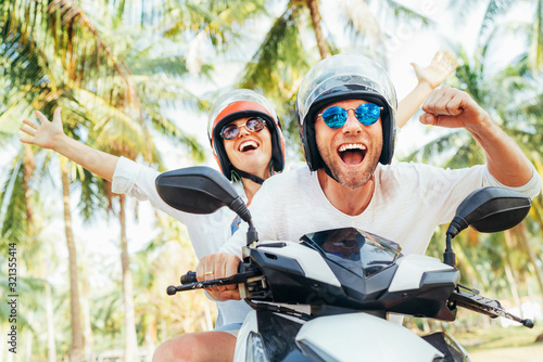 Fototapeta Happy smiling couple travelers riding motorbike scooter in safety helmets during tropical vacation under palm trees on Ko Samui island in Thailand obraz na płótnie