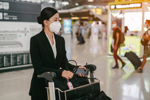 Women Withher Luggage And Trolley Is Wearing Medical Face Masks To Protect Themselves From Pollution, Germs And Coronavirus At The Airport.
