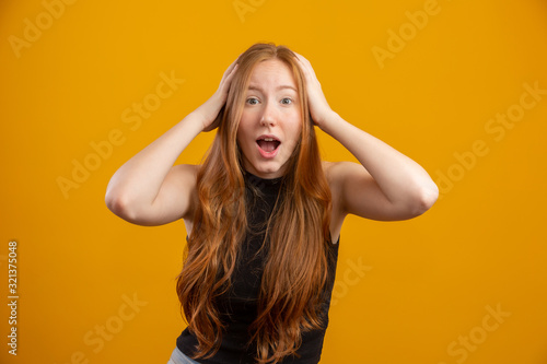 Fototapeta Young redhead woman raising hands to head, open-mouthed, feeling extremely lucky, surprised, excited and happy against yellow wall