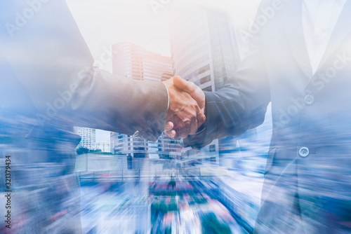 Double exposure businessman handshake to show cooperate in business with city scape building  background Wallpaper Mural