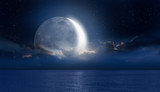 """Crescent moon over the tropical sea at night """"Elements of this image furnished by NASA"""