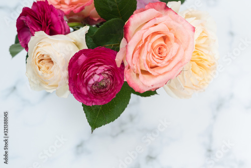 Blush and pink rose bouquet flat lay on marble background
