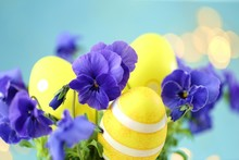 Easter Religious Holiday.Yellow Decorative Easter Eggs In Blue Colors Of Pansies On A Light Blue Background With Yellow Bokeh. Spring Floral Easter Background.