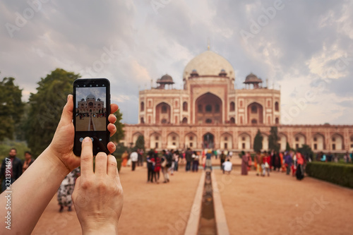 Tourist taking a picture in a smartphone of Humayun's tomb in Delhi, India Wallpaper Mural