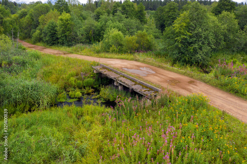 Top view of a country road and the collapsing old bridge over an overgrown river Fototapete