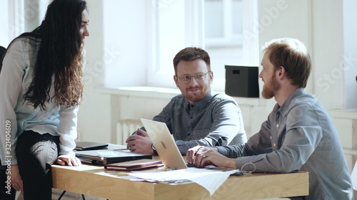 Happy relaxed young male boss businessman talking to smiling colleagues at modern loft office workplace table.