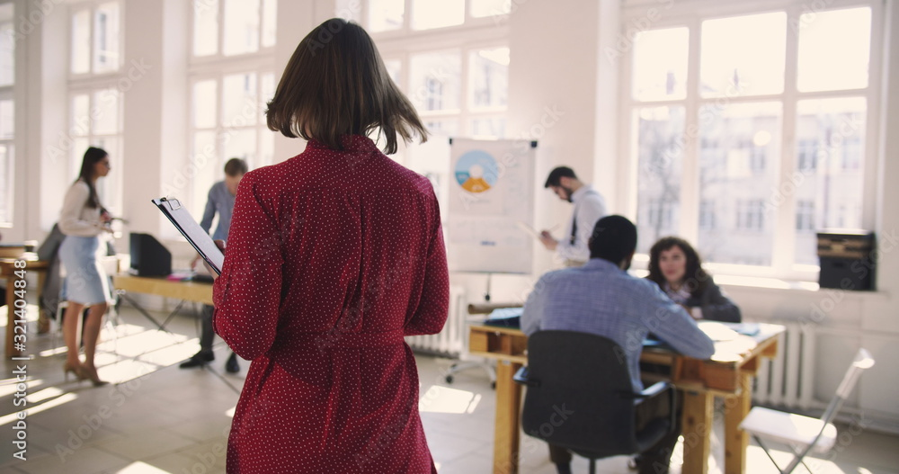 Fototapeta Camera follows middle aged business assistant woman in red dress entering large trendy loft office talking to colleagues