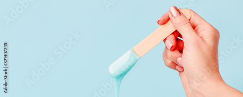 depilation and beauty concept - sugar paste or wax honey for hair removing with wooden waxing spatula sticks in hand on blue background, copy space, beauty industry, concept of smooth skin remove - 321407249