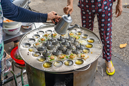 Fotomural Street food hawker making Vietnamese mini shrimp pancake- Banh Khot