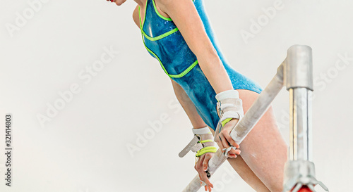 Fotografía girl gymnast exercise uneven bars in gymnastics on light background