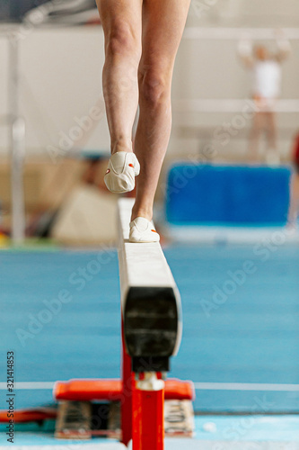 Fotomural girl gymnast point your toes on balance beam in gymnastics competition