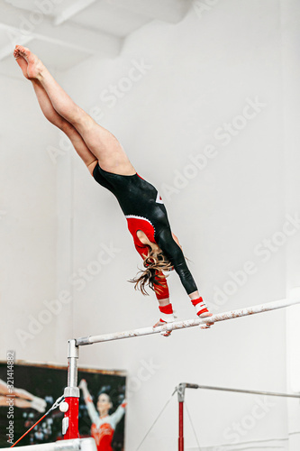 Cuadros en Lienzo young woman gymnast exercise on uneven bars in gymnastics