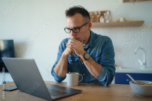 Thoughtful serious young man lost in thoughts in front of laptop, focused busine Fototapet