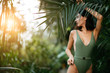 young attractive charming model around green fresh plants, slim slender female with short dark hair, posing at camera wearing green beautiful swimsuit or bikini. people and nature