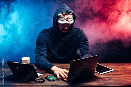 Fototapety, obrazy: hacker man in mask for sleeping sit with laptop try to get password or to enter pc system, genius engaged in crime. man use computer knowledge in order to access illegally in system and networks