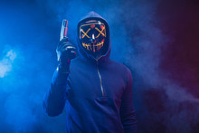Confident Dangerous Killer Male In Pullover Stand In The Hood With Gun, Anonymous Masked Hunter Man Isolated Over Smoky Space With Neon Lights. Crime, Kill, Hunt, Danger Concept