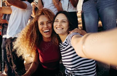 Female fans taking a selfie at a football match Wallpaper Mural