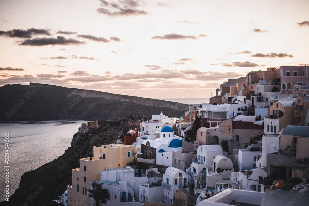 Fototapeta view of whitewashed houses and blue dome in oia Santorini Greece