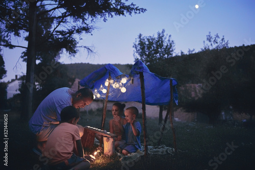 Father with children playing under their backyard tent. Canvas Print