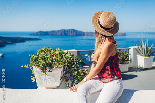 Fototapeta Woman traveler looking at Caldera landscape from Thera, Santorini island, Greece. Tourism, traveling, vacation obraz